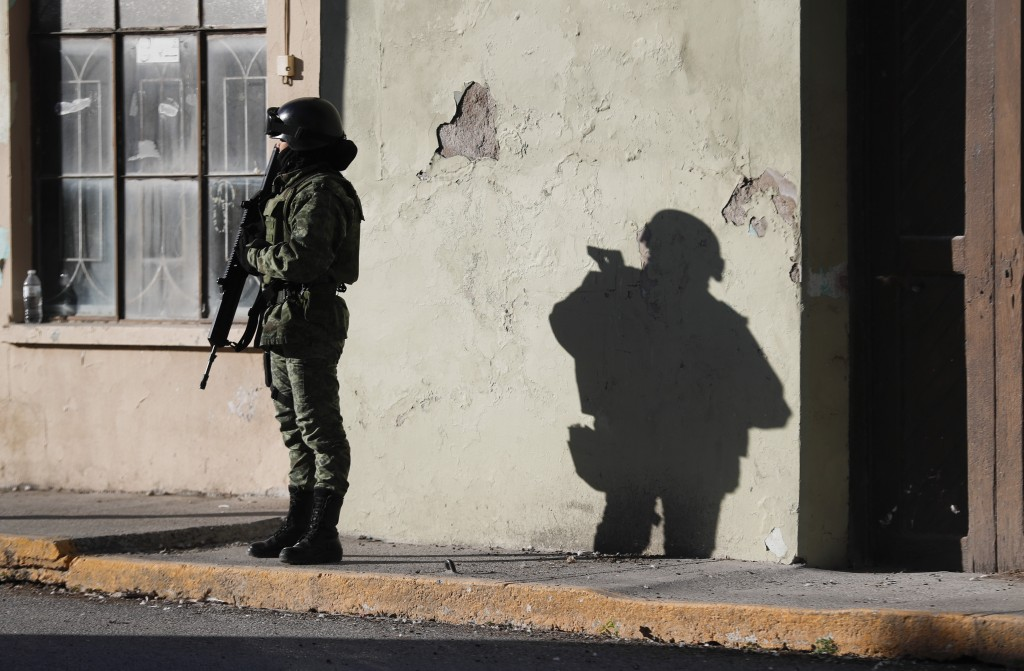 A member of the Mexican security forces stands guard near City Hall in Villa Union, Mexico, Tuesday, Dec. 3, 2019. Some long for the days when Mexican...