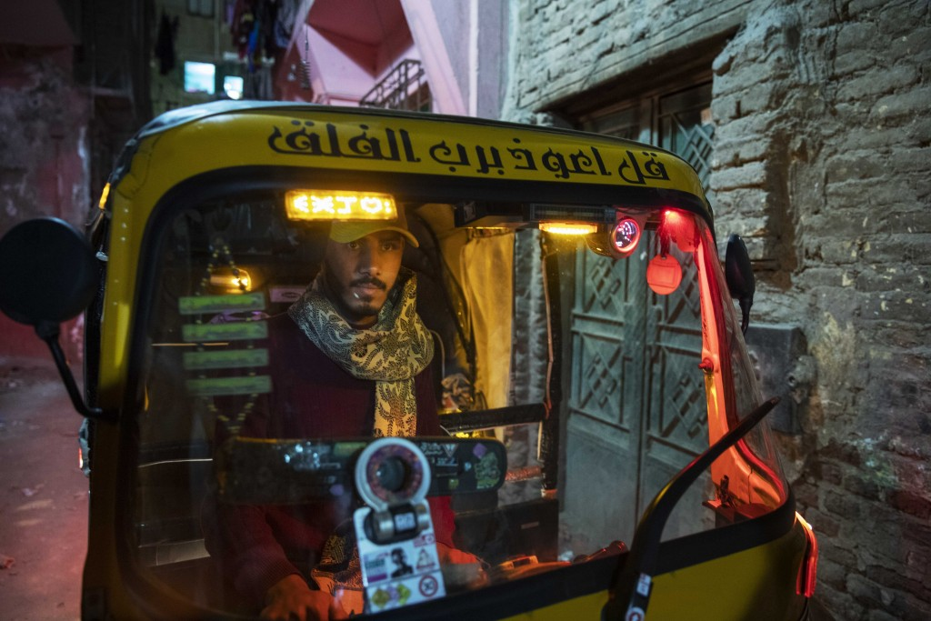 In this Nov. 19, 2019 photo, a driver maneuvers his tuk-tuk in a narrow alleyway of a slum in Cairo, Egypt. Motorized rickshaws known as tuk-tuks have...