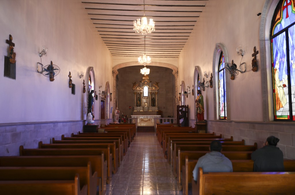 People pray inside the church in Villa Union, Mexico, Tuesday, Dec. 3, 2019. Villa Union bears the scars of the hourslong gun battles Saturday and Sun...
