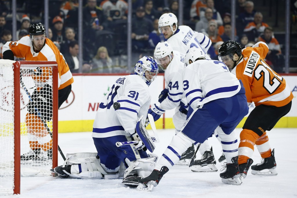 Philadelphia Flyers' Scott Laughton (21) scores a goal past Toronto Maple Leafs' Frederik Andersen (31) as Justin Holl (3) and Morgan Rielly (44) defe...