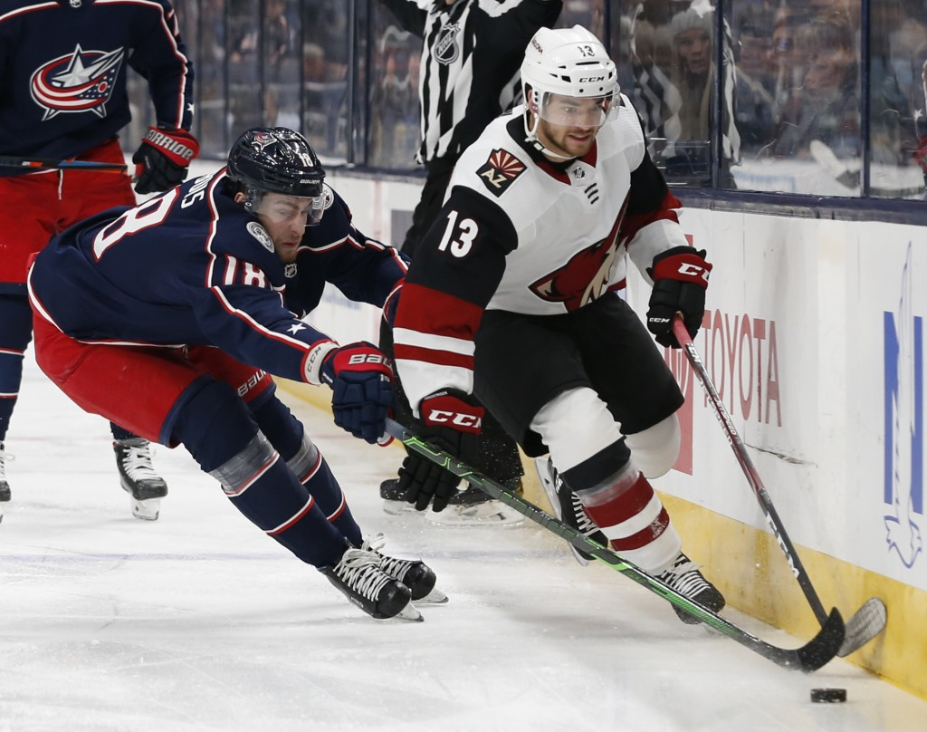 Arizona Coyotes' Vinnie Hinostroza, right, carries the puck across the blue line as Columbus Blue Jackets' Pierre-Luc Dubois defends during the first ...