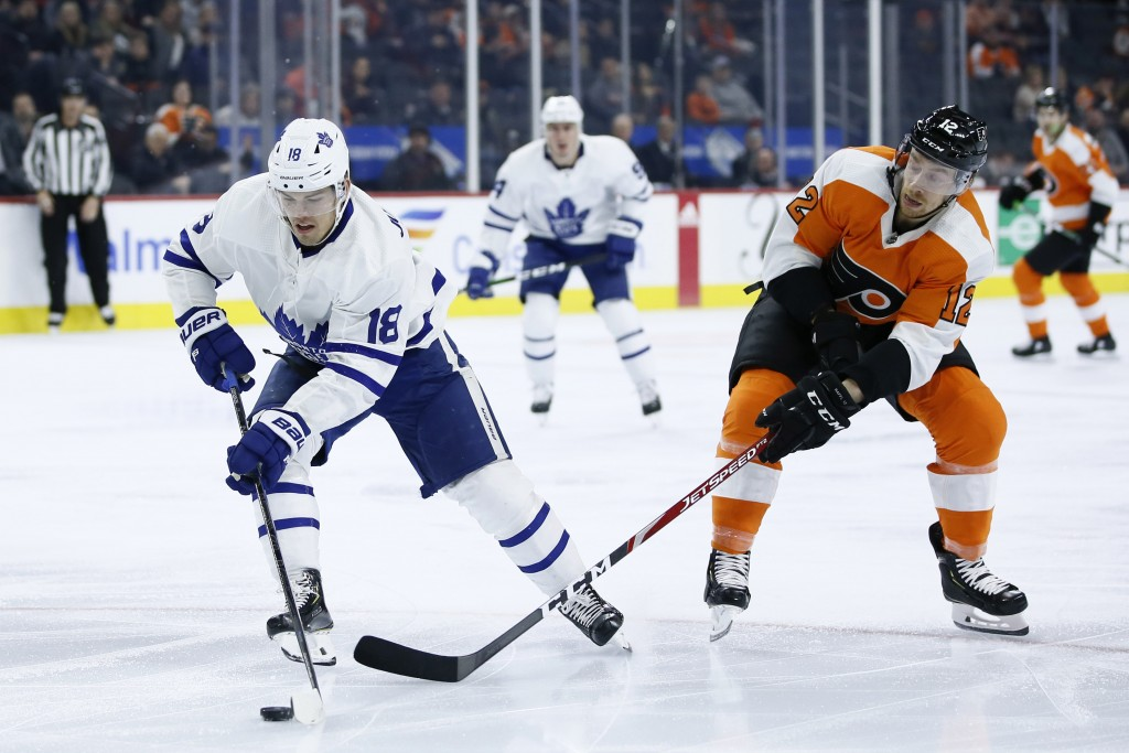Toronto Maple Leafs' Andreas Johnsson (18) tries to keep the puck away from Philadelphia Flyers' Michael Raffl (12) during the first period of an NHL ...