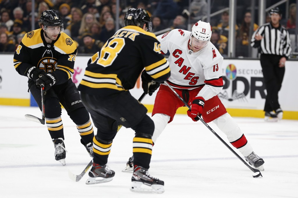 Boston Bruins' Matt Grzelcyk (48) defends against Carolina Hurricanes' Warren Foegele (13) during the first period of an NHL hockey game in Boston, Tu...