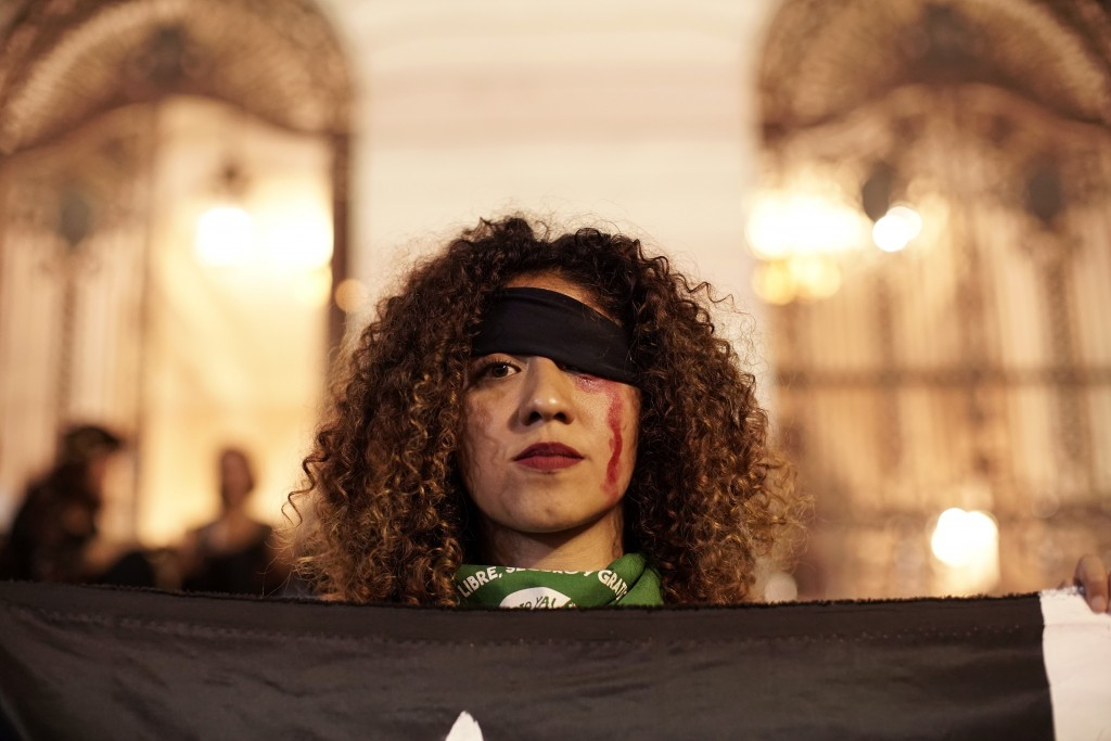 """A women takes part in the performance, """"Un violador en tu camino"""" or """"A rapist in your path,""""  in a demonstration against gender-based violence,  at C..."""