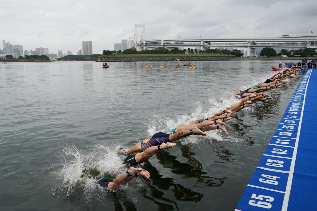 FILE - In this Aug. 15, 2019, file photo, athletes dive into the water at the start line during a women's triathlon test event at Odaiba Marine Park, ...