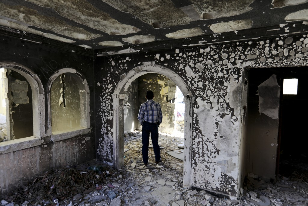 A former policeman walks through an abandoned home, torched by the Zetas cartel eight years back, in Allende, Coahuila state, Mexico, Tuesday, Dec. 3,...