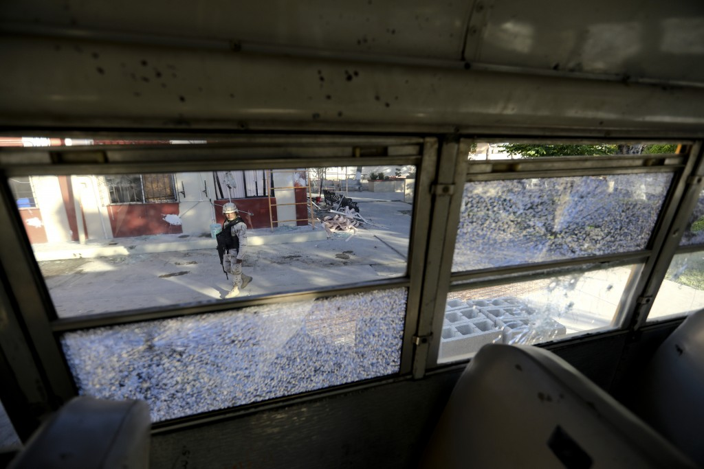 A soldier walks past City Hall that is riddled with bullet holes after a weekend gun battle, in Villa Union, Mexico, Tuesday, Dec. 3, 2019. Villa Unio...