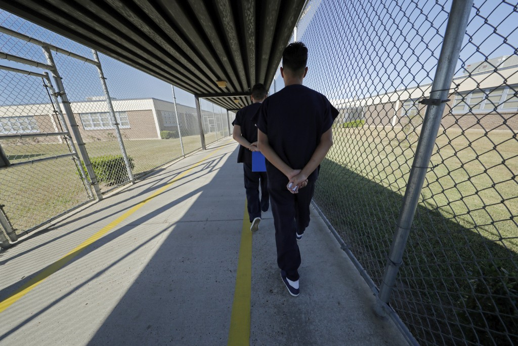 FILE - In a Thursday, Sept. 26, 2019 file photo, detainees walk with their hands clasped behind their backs along a line painted on a walkway inside t...