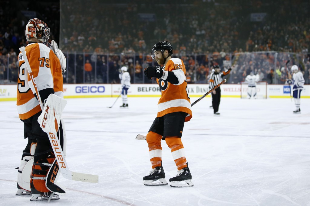Philadelphia Flyers' Claude Giroux (28) celebrates with Carter Hart (79) after a goal during the third period of an NHL hockey game against the Toront...