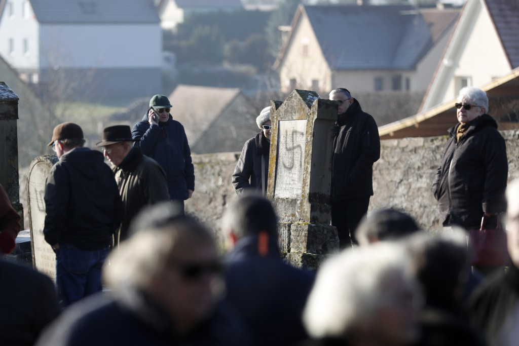 Members of the Jewish community walk amid vandalized tombs in the Jewish cemetery of Westhoffen, west of the city of Strasbourg, eastern France, Wedne...