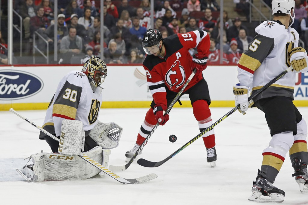 Vegas Golden Knights goaltender Malcolm Subban (30) watches the puck as it bounces in front of New Jersey Devils center Travis Zajac (19) with Golden ...