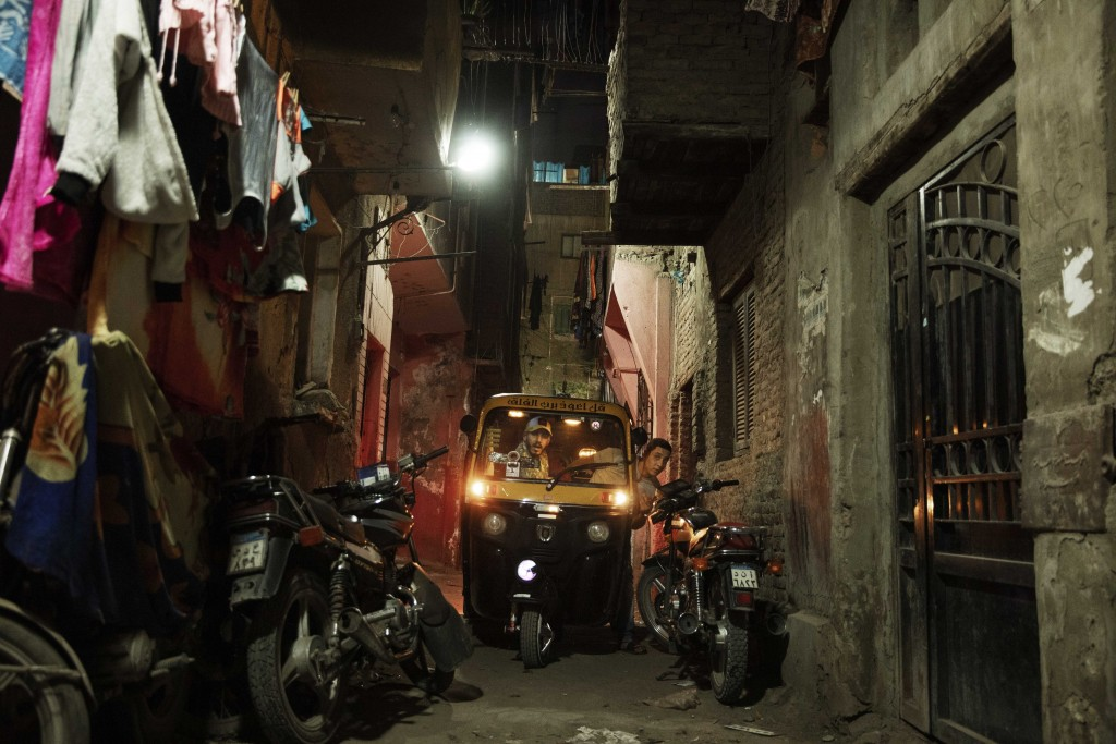 In this Nov. 19, 2019 photo, a driver tries to maneuver his tuk-tuk in a narrow alleyway of a slum in Cairo, Egypt. Motorized rickshaws known as tuk-t...