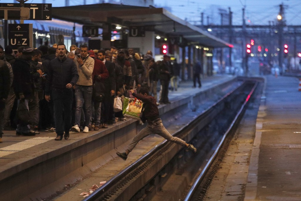 FILE - In this Tuesday, April 3, 2018 file photo a passenger crosses railroad tracks at rush hour at Gare de Lyon train station, in Paris. France's ra...