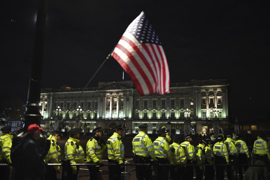 A supporter of President Donald Trump waves the U.S. flag outside Buckingham Palace in London, Tuesday, Dec. 3, 2019. Trump and his NATO counterparts ...