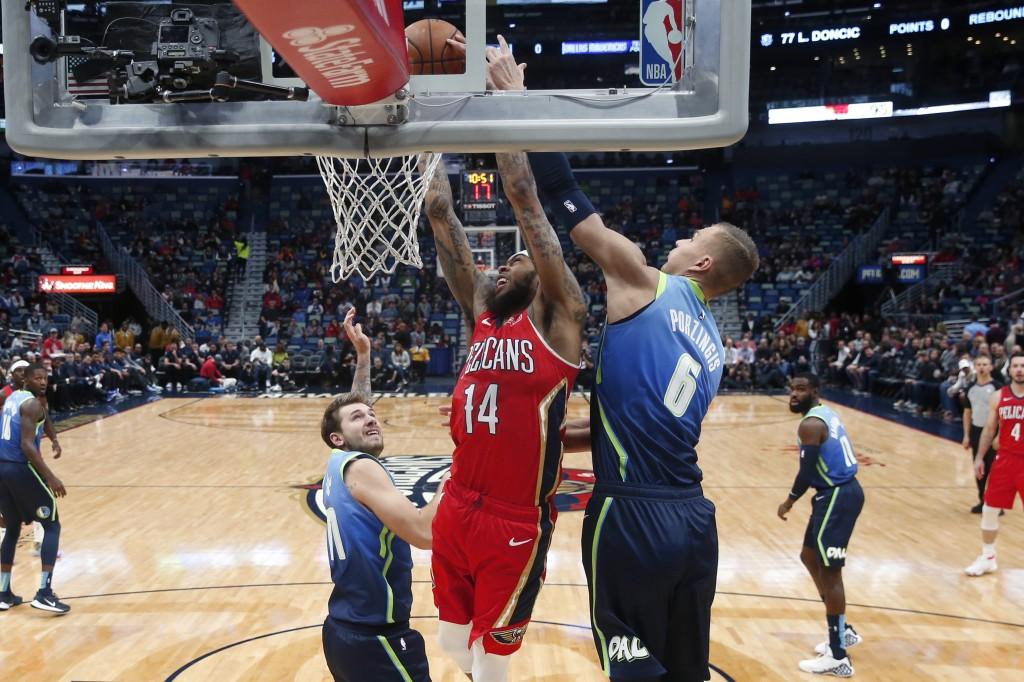 New Orleans Pelicans forward Brandon Ingram (14) goes to the basket against Dallas Mavericks forward Kristaps Porzingis (6) in the first half of an NB...