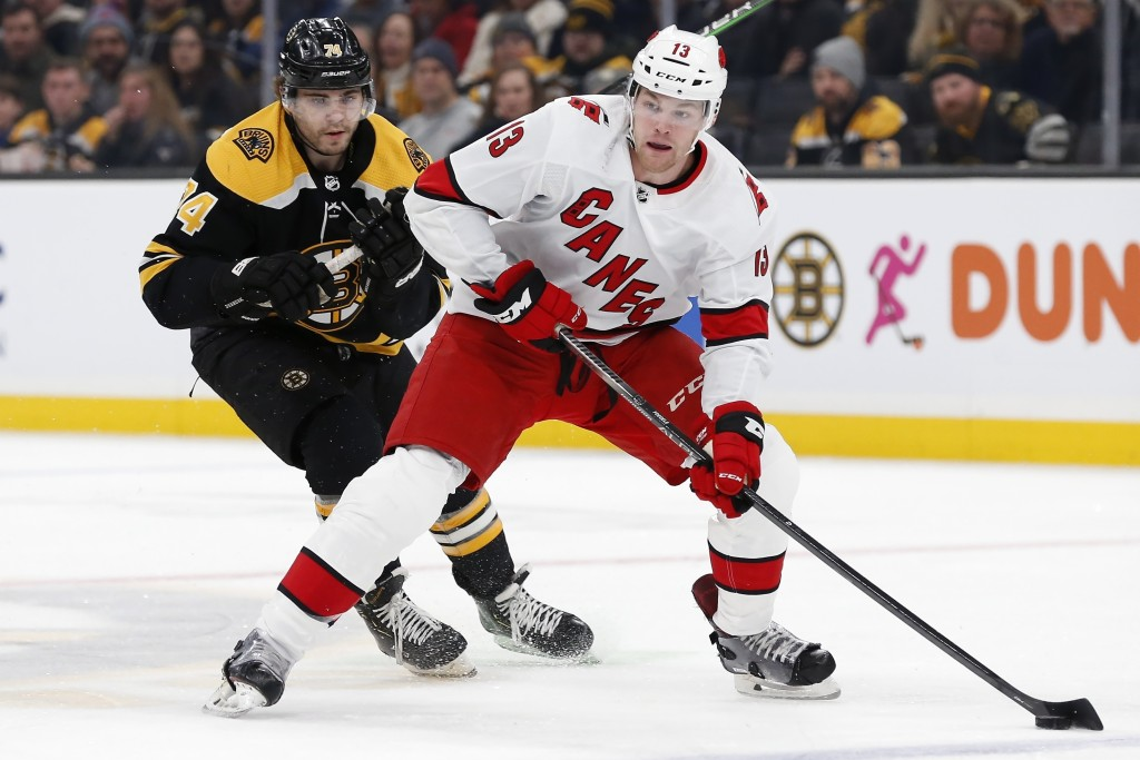 Carolina Hurricanes' Warren Foegele (13) handles the puck in front of Boston Bruins' Jake DeBrusk (74) during the first period of an NHL hockey game i...