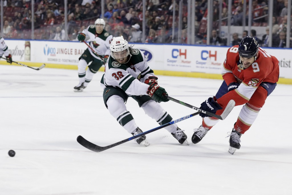 Minnesota Wild right wing Ryan Hartman (38) and Florida Panthers center Brian Boyle (9) chase the puck during the second period of an NHL hockey game,...