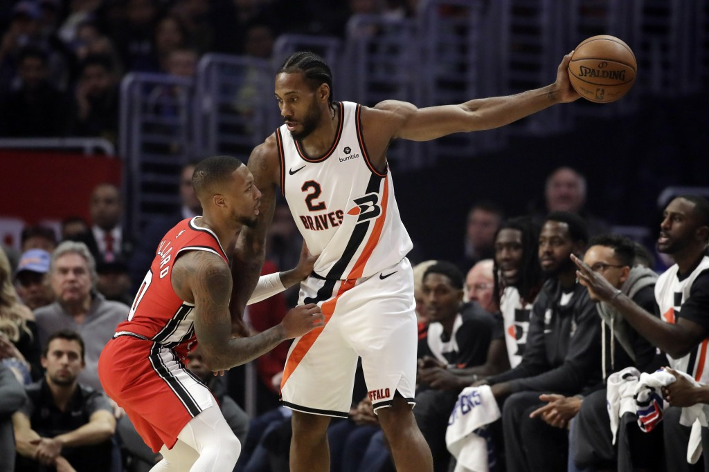 Portland Trail Blazers' Damian Lillard, left, defends on Los Angeles Clippers' Kawhi Leonard (2) during the first half of an NBA basketball game Tuesd...