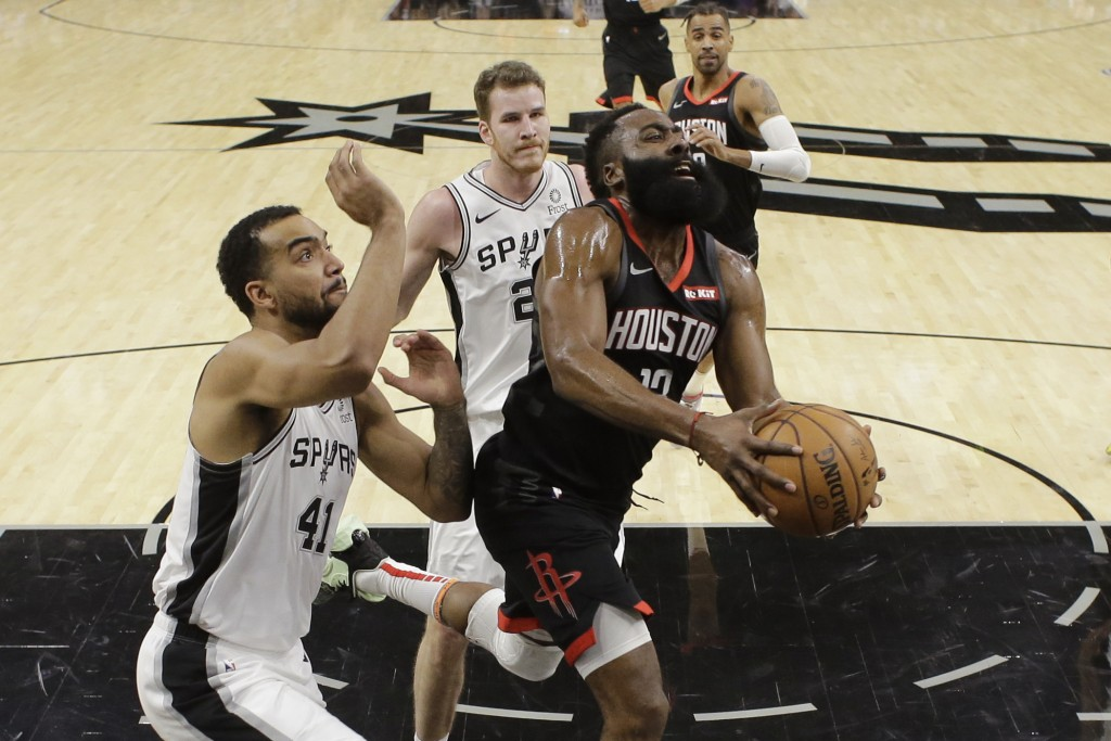 Houston Rockets guard James Harden (13) drives past San Antonio Spurs forward Trey Lyles (41) and center Jakob Poeltl (25) during the first half of an...