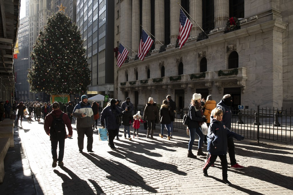 People walk by the New York Stock Exchange, Tuesday, Dec. 3, 2019. Stocks fell broadly Tuesday after President Donald Trump cast doubt over the potent...