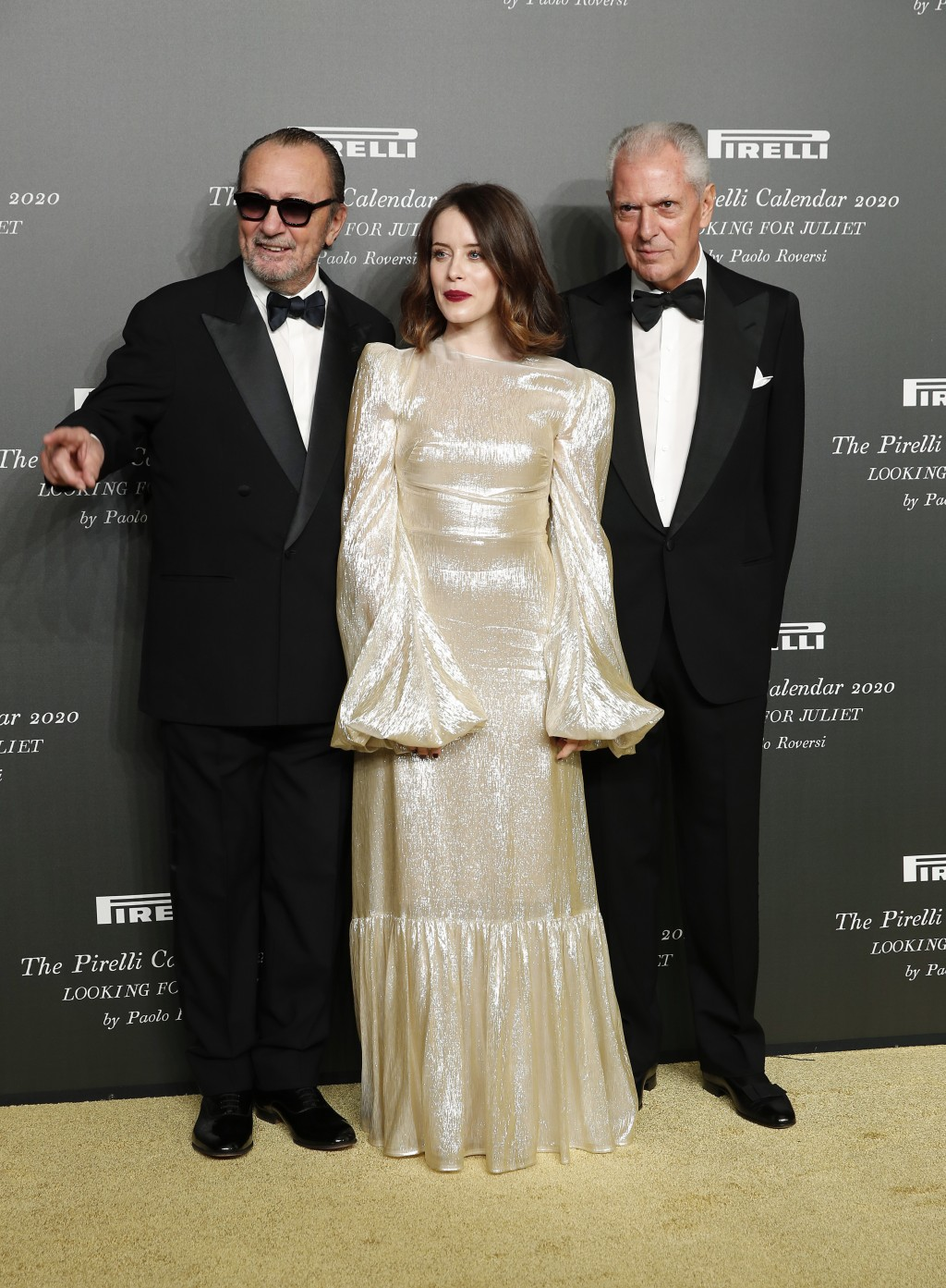 British actress Claire Foy, center, poses with Italian photographer Paolo Roversi, left, and Pirelli CEO Marco Tronchetti Provera, at the 2020 Pirelli...