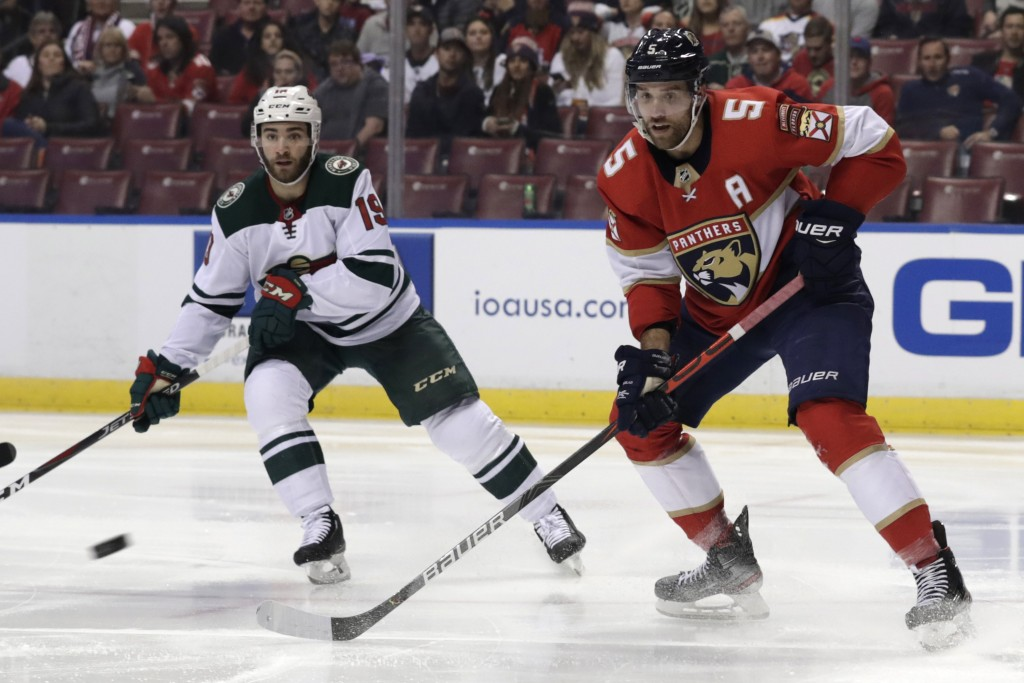 Minnesota Wild center Luke Kunin (19) and Florida Panthers defenseman Aaron Ekblad (5) watch the puck during the first period of an NHL hockey game, T...