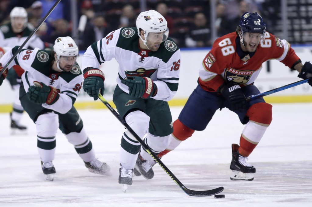 Minnesota Wild left wing Jason Zucker (16) skates with the puck as Florida Panthers center Mike Hoffman (68) defends during the second period of an NH...
