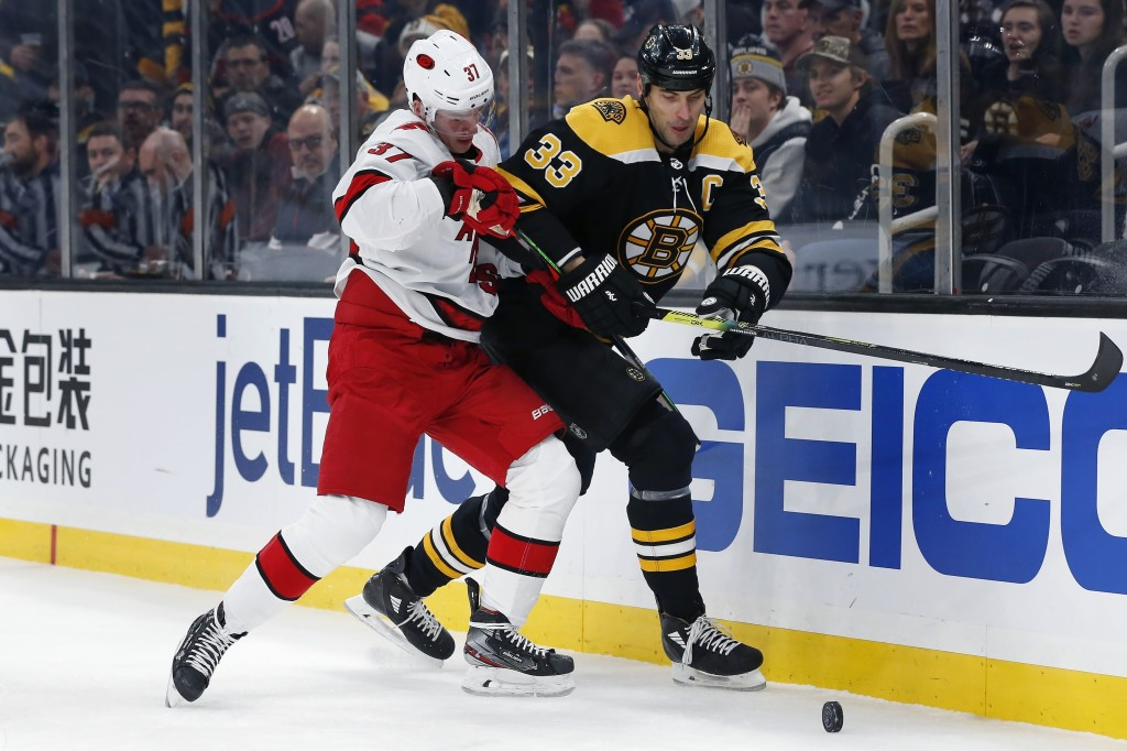 Carolina Hurricanes' Andrei Svechnikov (37) and Boston Bruins' Zdeno Chara (33) compete for the puck during the first period of an NHL hockey game in ...