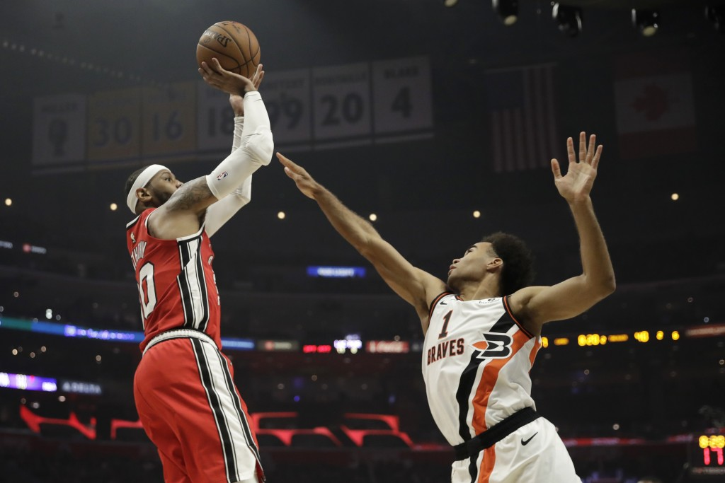 Portland Trail Blazers' Carmelo Anthony, left, shoots over Los Angeles Clippers' Jerome Robinson (1) during the first half of an NBA basketball game T...