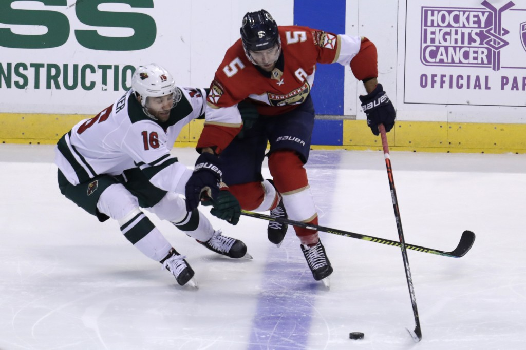 Minnesota Wild left wing Jason Zucker (16) and Florida Panthers defenseman Aaron Ekblad (5) fight for the puck during the third period of an NHL hocke...