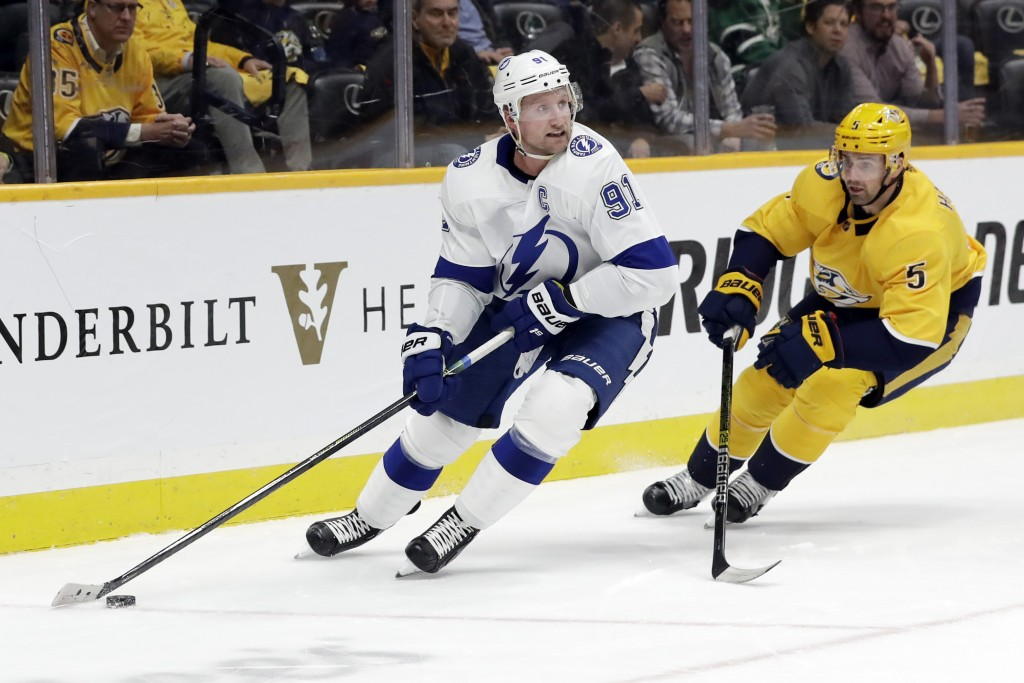 Tampa Bay Lightning center Steven Stamkos (91) is followed by Nashville Predators defenseman Dan Hamhuis (5) in the first period of an NHL hockey game...