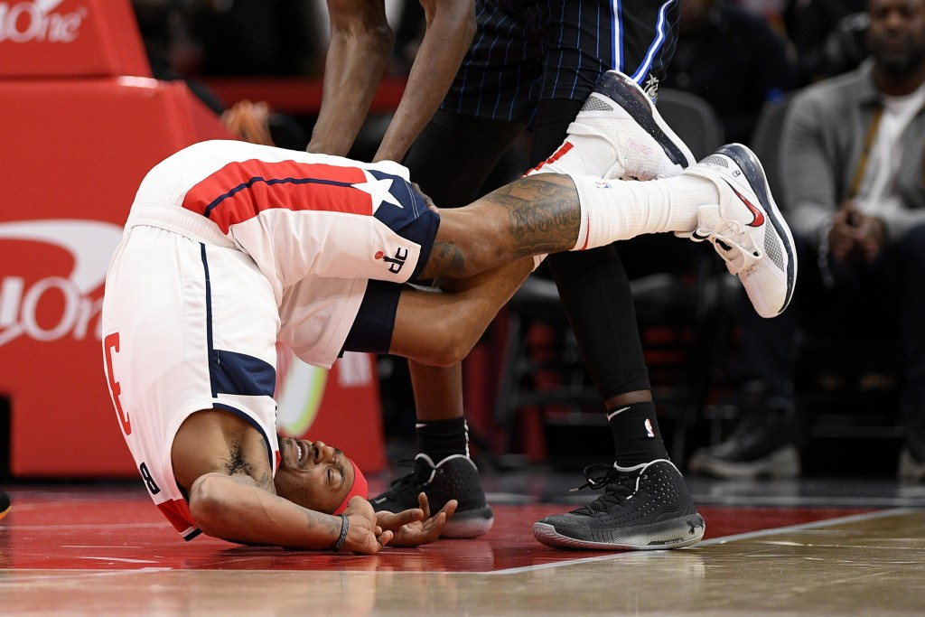 Washington Wizards guard Bradley Beal (3) tumbles on the court during the first half of an NBA basketball game against the Orlando Magic, Tuesday, Dec...