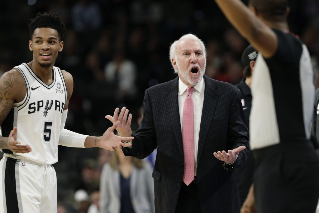 San Antonio Spurs coach Gregg Popovich, center, and guard Dejounte Murray (5) question a call during the first half of the team's NBA basketball game ...