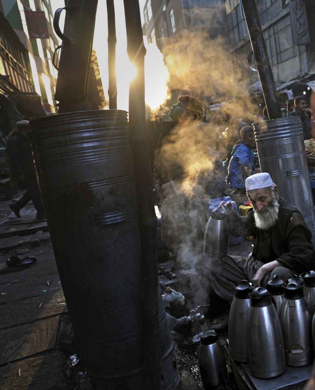 Afghan tea seller Farooq Shah, center, fills kettles with tea for customers at a market place in Kabul, Afghanistan, Wednesday, Dec. 4, 2019. (AP Phot...