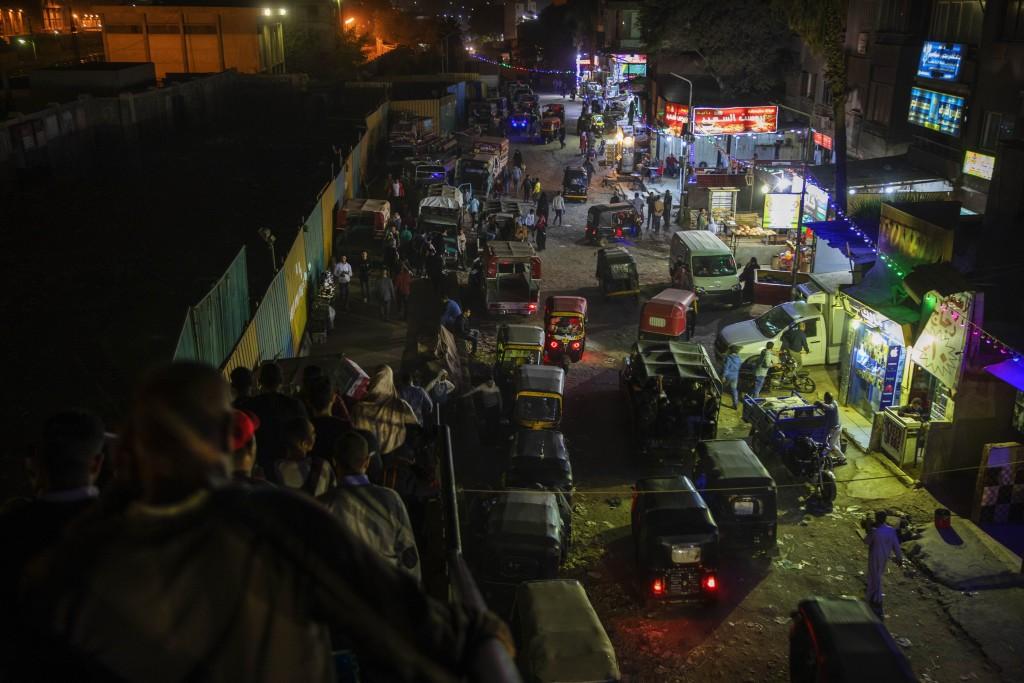 In this Nov. 24, 2019 photo, tuk-tuk drivers make their way on a crowded street at a slum area in Cairo, Egypt. Motorized rickshaws known as tuk-tuks ...