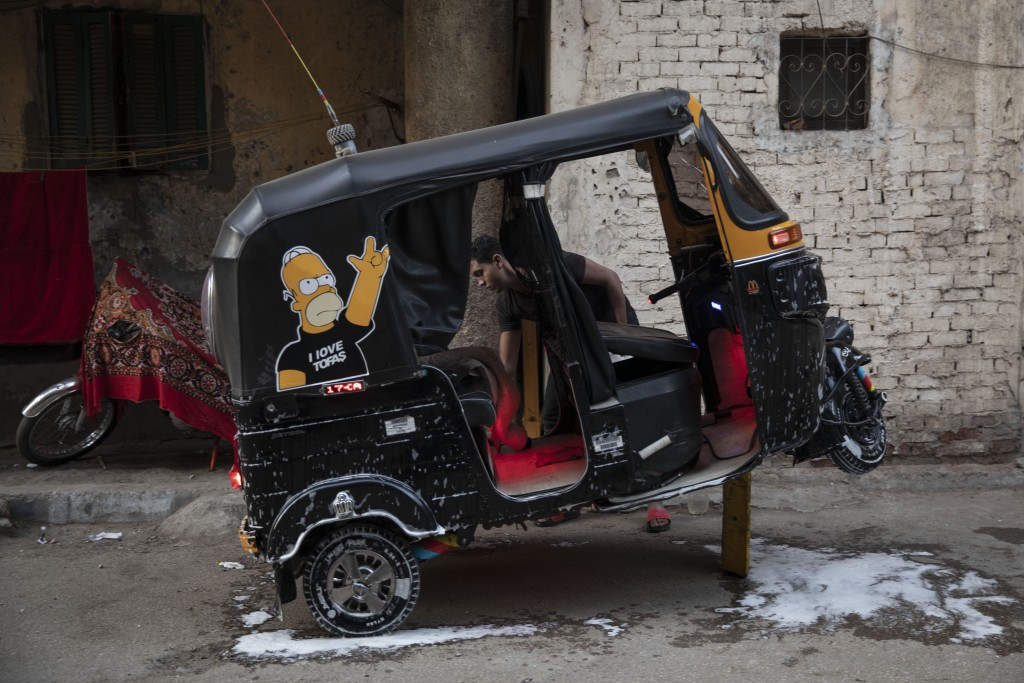 In this Nov. 19, 2019 photo, a tuk-tuk driver washes his vehicle in an alleyway of a slum in Cairo, Egypt. Motorized rickshaws known as tuk-tuks have ...