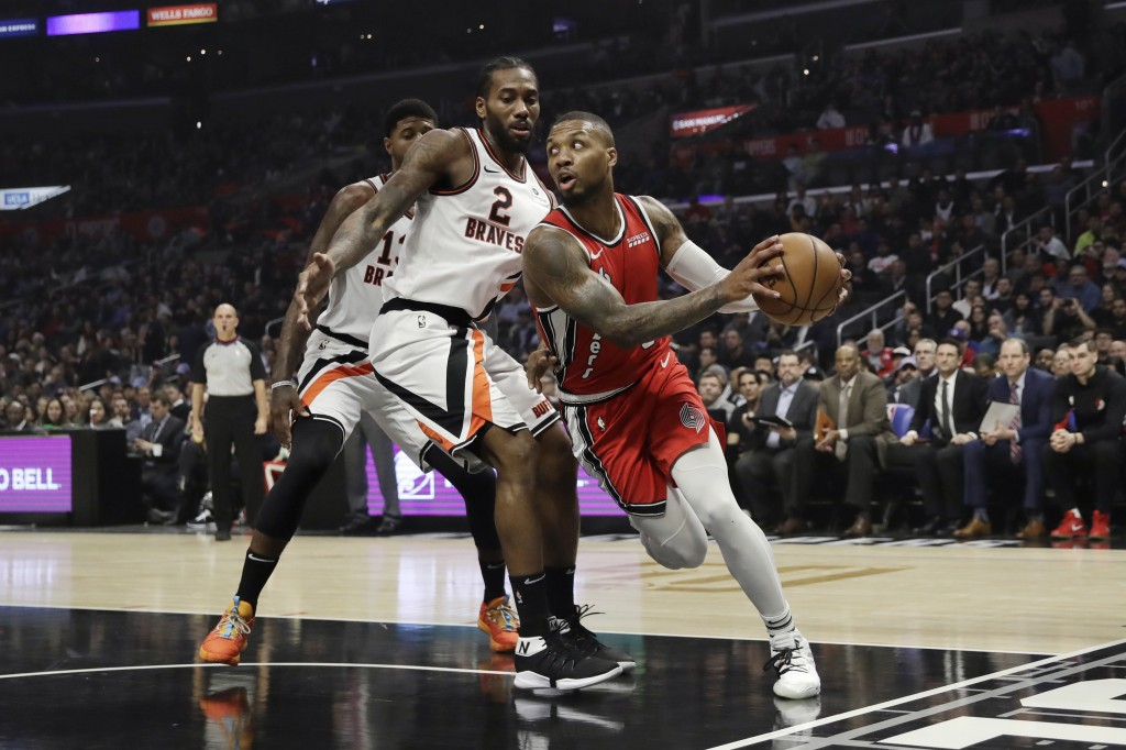 Portland Trail Blazers' Damian Lillard, right, looks to pass under the basket as Los Angeles Clippers' Kawhi Leonard (2) defends during the first half...