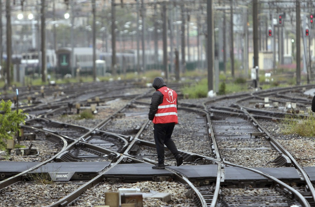 FILE - In this May 14, 2018 file photo, a striking rail worker walks on the tracks of the Saint-Charles train station, in Marseille, southern France. ...