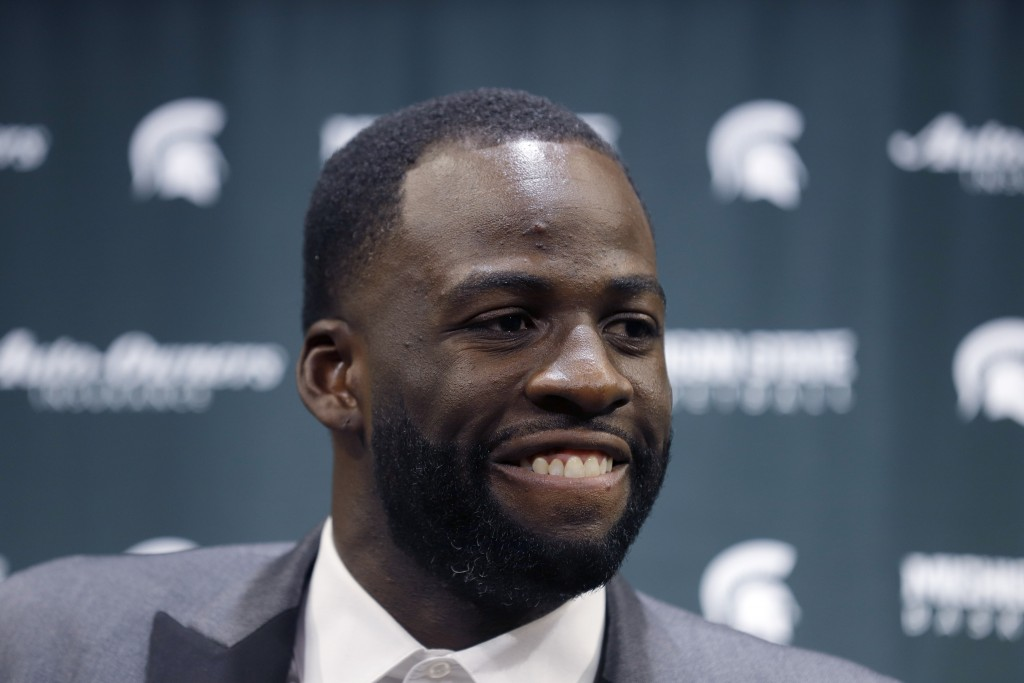 Former Michigan State and current Golden State Warriors player Draymond Green talks to reporters before an NCAA college basketball Tuesday, Dec. 3, 20...