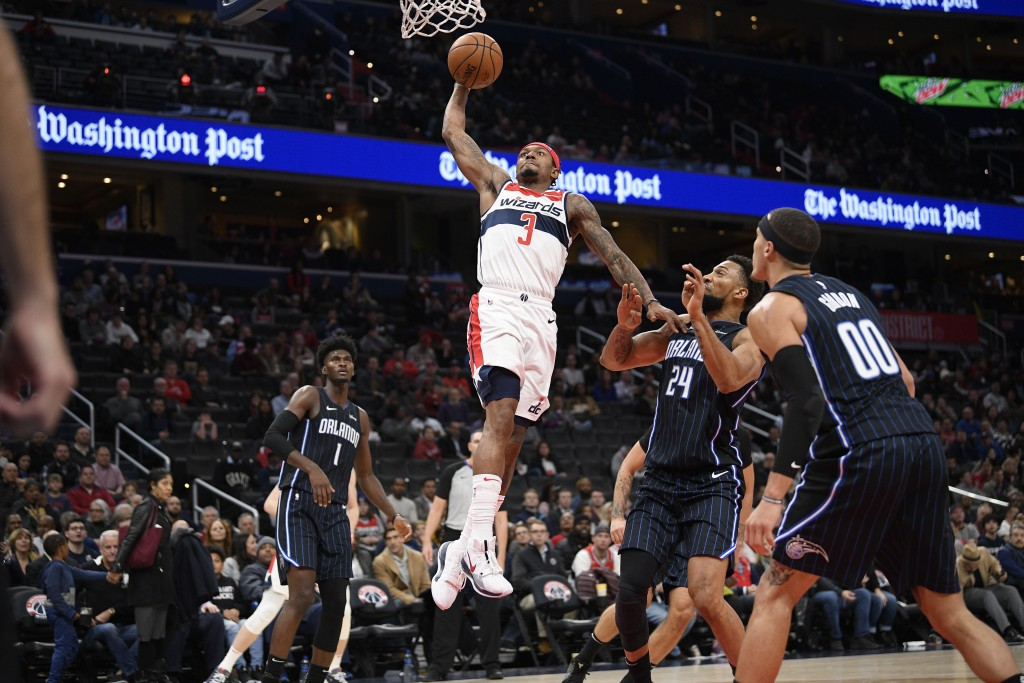 Washington Wizards guard Bradley Beal (3) goes to the basket past Orlando Magic forward Jonathan Isaac (1), forward Aaron Gordon (00), and center Khem...