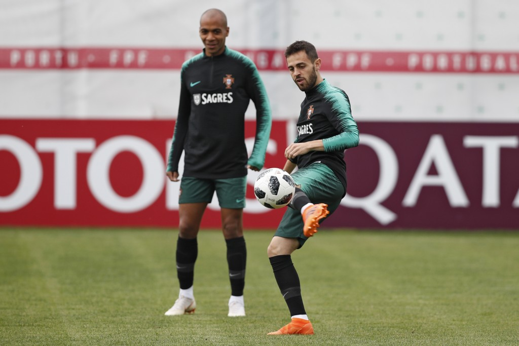 FILE - In this Wednesday, June 13, 2018 file photo, Portugal's Bernardo Silva, right, plays the ball next to teammate Joao Mario during the training s...