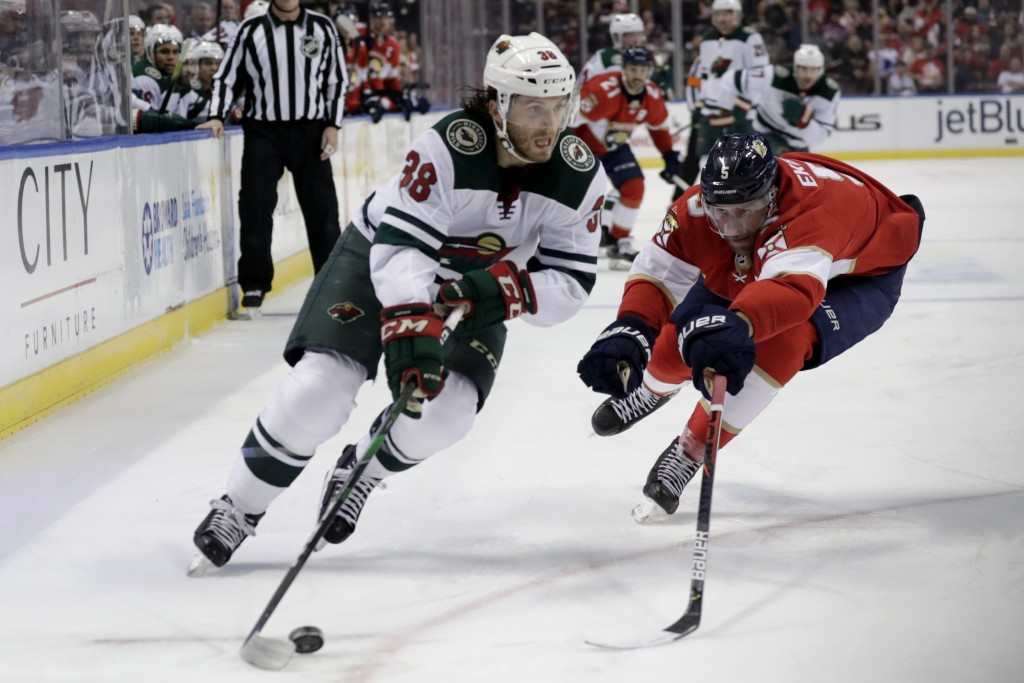 Minnesota Wild right wing Ryan Hartman (38) skates with the puck as Florida Panthers defenseman Aaron Ekblad defends during the second period of an NH...