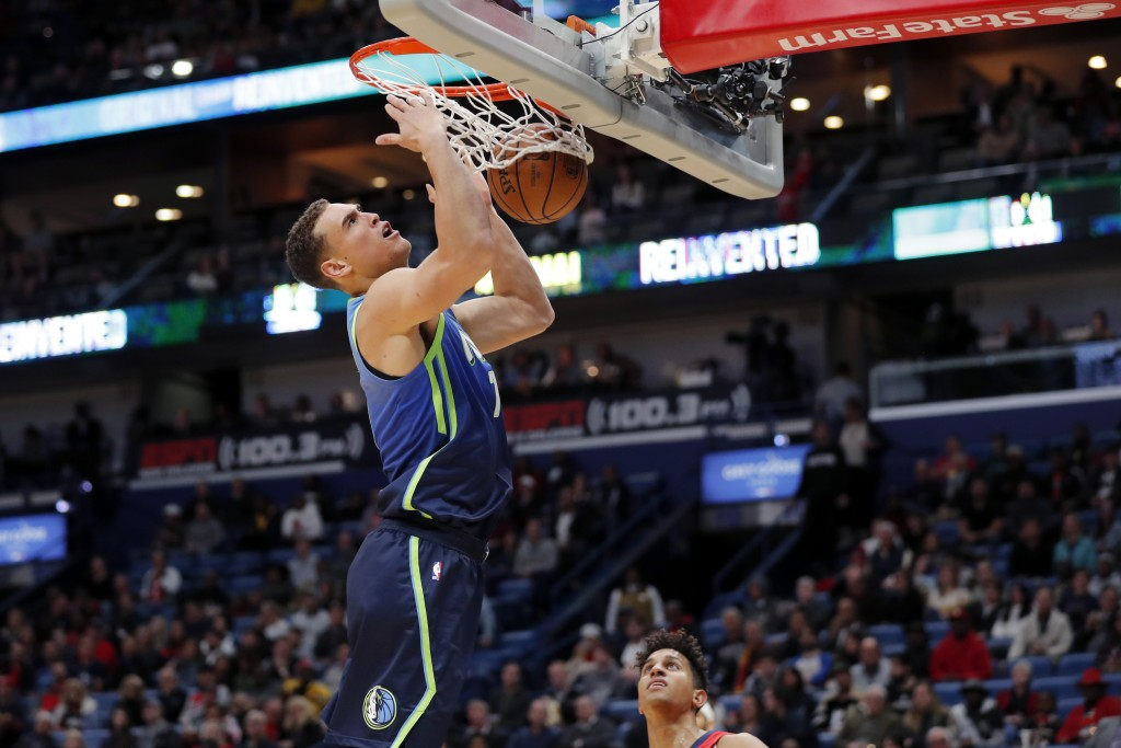 Dallas Mavericks forward Dwight Powell (7) slam dunks over New Orleans Pelicans guard Frank Jackson in the first half of an NBA basketball game in New...