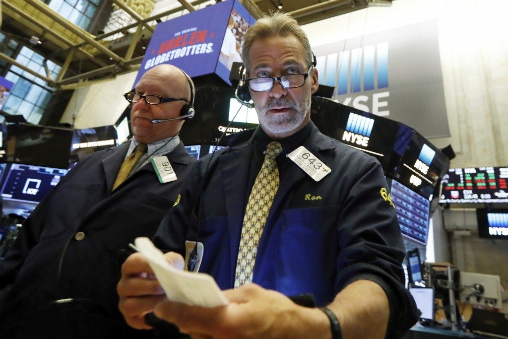 FILE - In this Nov. 20, 2019, file photo traders John Doyle, left, and Ronald Madarasz work on the floor of the New York Stock Exchange. The U.S. stoc...