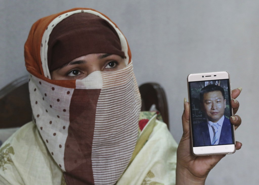 FILE - In this May 22, 2019 file photo, Sumaira a Pakistani woman, shows a picture of her Chinese husband in Gujranwala, Pakistan. Sumaira, who didn't...