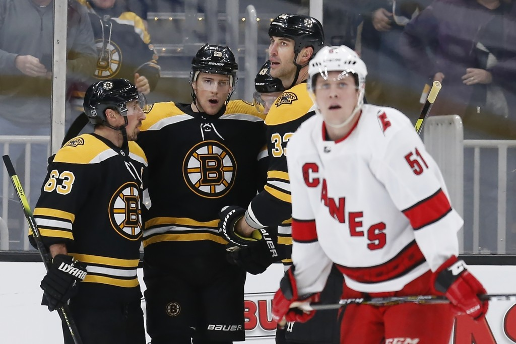 Boston Bruins' Charlie Coyle (13) celebrates his goal as Carolina Hurricanes' Jake Gardiner (51) skates away during the third period of an NHL hockey ...