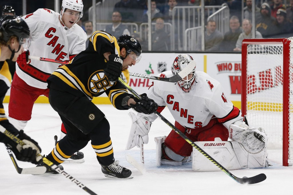 Boston Bruins' Brad Marchand tries to get a shot on Carolina Hurricanes' James Reimer during the second period of an NHL hockey game in Boston, Tuesda...