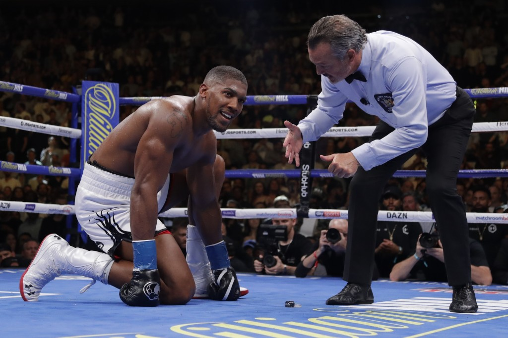 FILE - In this Saturday, June 1 , 2019 file photo, Britain's Anthony Joshua reacts as the referee counts for him after he was knocked down during the ...