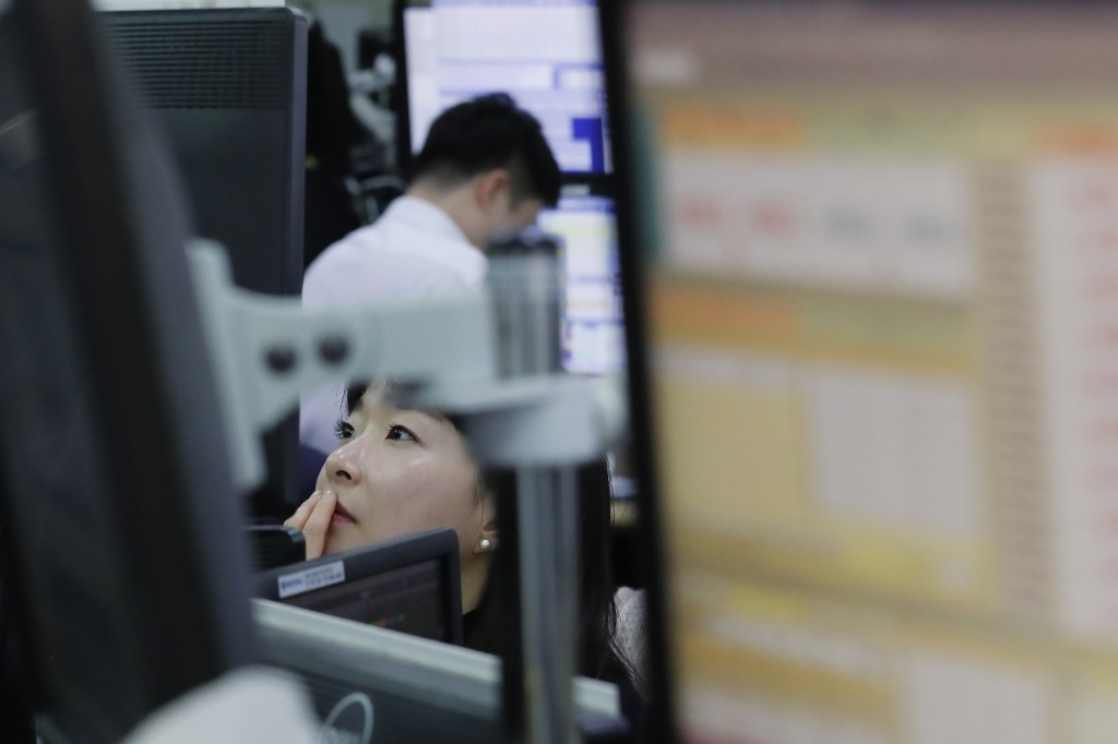 A currency trader watches monitors at the foreign exchange dealing room of the KEB Hana Bank headquarters in Seoul, South Korea, Wednesday, Dec. 4, 20...