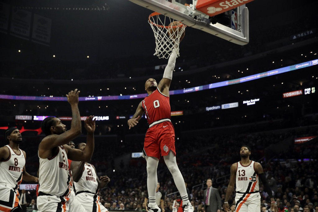 Portland Trail Blazers' Damian Lillard (0) dunks against the Los Angeles Clippers during the first half of an NBA basketball game Tuesday, Dec. 3, 201...